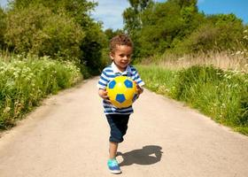 litet barn som håller en boll foto