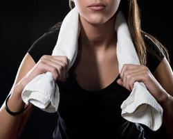 fitness tjej med handduk isolerad på svart detalj foto