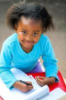 söt afrikansk student som skriver i anteckningsboken vid skrivbordet.