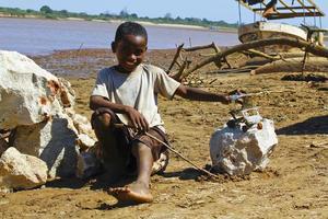 liten afrikansk pojke, utomhus och leker med en bil foto