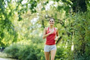 ung vacker idrottsman som joggar i park foto