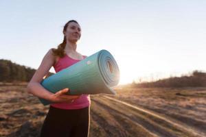 kvinna som går med en yogamatta utanför under solnedgången