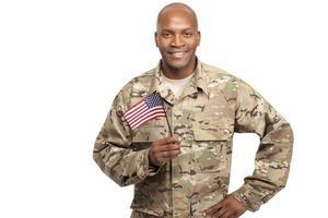glad serviceman som innehar en amerikansk flagga foto