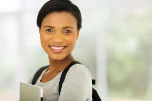 ung afrikansk amerikan högskolestudent håller bärbar dator foto