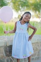 flicka utomhus med rosa ballong foto