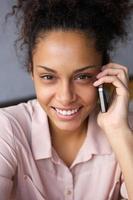 glad afroamerikansk kvinna som använder mobiltelefon foto