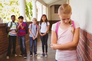 ledsen skolflicka med vänner i bakgrunden på skolakorridoren foto