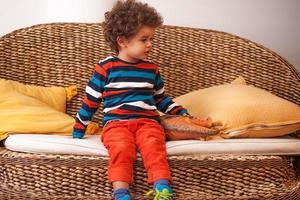 söt pojke som sitter i ett vardagsrum foto