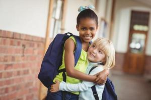 söta elever som omfamnar vid korridoren foto
