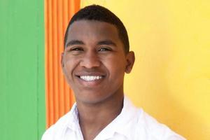 glad karibisk kille framför en färgglad vägg foto