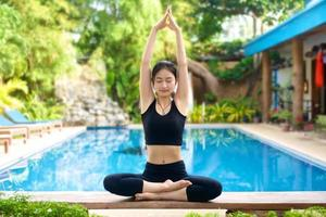 asiatisk tjej som utövar yoga på en bänk foto
