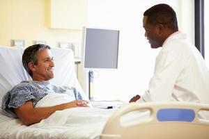 läkare pratar med manlig patient på sjukhusrum foto
