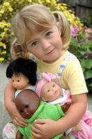 tjej med multi = etniska dockor foto