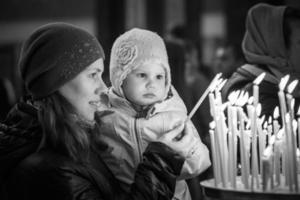 mamma med lilla dotter i ortodoxa kyrkan foto