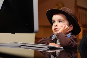 """uttråkad barn """"affärsman"""" på datortangentbordet foto"""