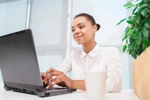 söt mulatt tjej som arbetar på datorn foto