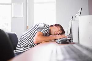 student som sover på datorn i klassrummet foto