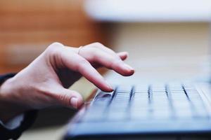 mänsklig hand kommer att trycka på tangenten på tangentbordet foto