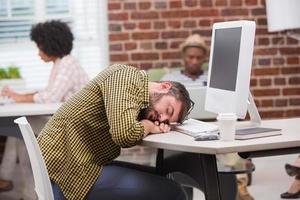 avslappnad man vilar huvudet på datorns tangentbord foto