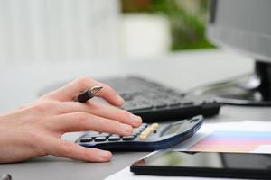 detalj av händer som skriver på miniräknare med stationära datortangentbord foto