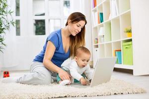 ung attraktiv mor och baby med hjälp av dator foto