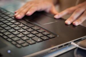 detalj av händer som arbetar på datortangentbordet foto