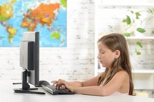 skolflicka med en dator i klassrummet foto
