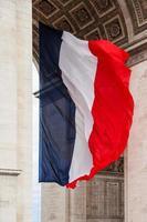 Frankrikes nationella flagga med detalj av triumfbågen, Paris, Frankrike foto