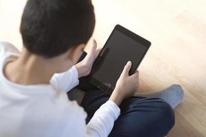 ung pojke som sitter med mobil surfplatta foto