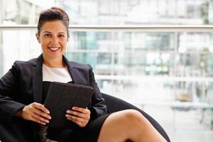 affärskvinna håller tablet PC, ser till kameran