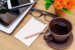 bärbar dator och kopp kaffe med blomma på skrivbordet foto