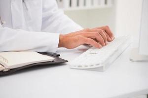 läkare skriver på tangentbordet och foto