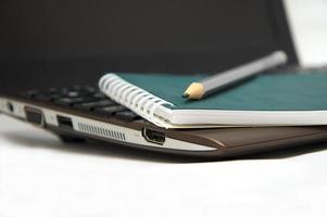 anteckningsbok med penna på det bruna bärbara tangentbordet foto
