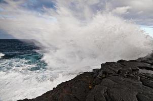 vågor kraschar mot klippan foto