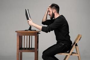 rolig och galen man som använder en dator foto