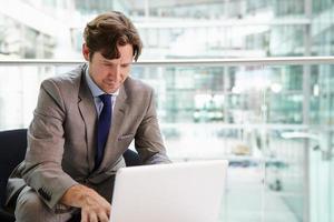 företags affärsman som använder bärbar dator, midja upp foto