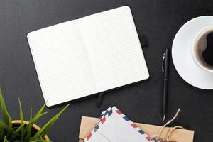 skrivbord med dator, leveranser, kaffe och blomma foto