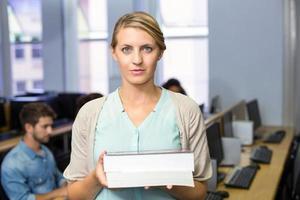 kvinnlig lärare som håller böcker i datorklass foto