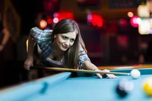 ung vacker ung dam som syftar till att ta snookerskottet foto