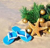 julgran med julgranskulor, tofflor, sjöstjärna på stranden foto