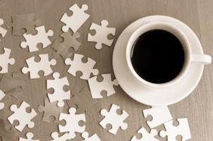 kopp kaffe och pusselbitar på bordet foto