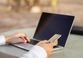 affärsman som arbetar med mobiltelefon och bärbar dator