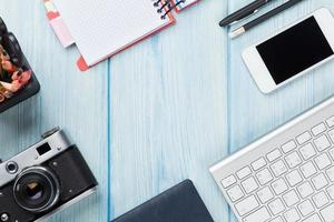 skrivbord bord med dator, leveranser och kamera foto