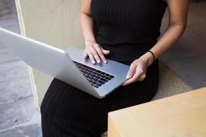 ung kvinnlig frilansare som ansluter till internet via dator foto