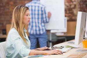 koncentrerad kvinnlig fotoredigerare som använder datorn på kontoret foto