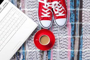 kopp cappuccino nära röda gumssko och dator foto