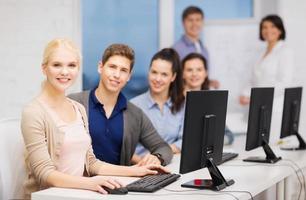 grupp leende studenter med datorer i skolan foto