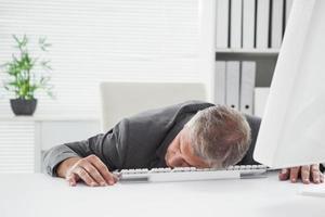 utmattad affärsman som sover vid sitt skrivbord foto