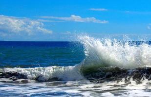 havsvågor som bryter på stranden foto