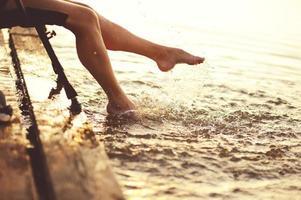 ung kvinna vid floden på kvällssolnedgången, foto